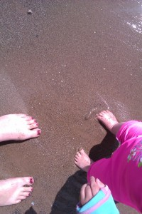 """an adult's and a child's feet on a sandy beach"""