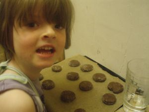 """Small girl next to a baking tray of uncooked biscuits"""