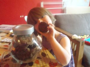 """Small girl next to a jar of biscuits, holding one up so it hides her mouth"""