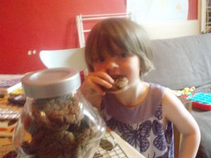 """Girl next to biscuit jar biting into a molasses cookie"""