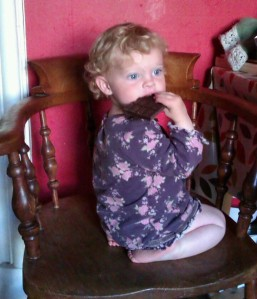 """a small blonder toddler eats some chocolate while kneeling on a chair"""