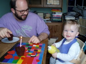 """""""a chocolate muffin has a candle in it and a 1 year old baby is smilling for the camera. In the background her father is pointing at the camera while looking at the baby"""""""