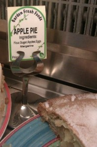 """An apple pie with a sign next to it listing the ingredients"""