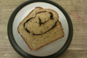 """A piece of bread with a chocolae swirl in the middle sitting on a plate"""
