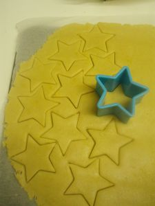 """Some biscuit dough cut into stars with a blue cutter"""