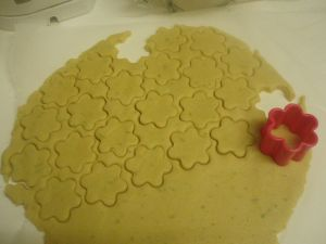 """Some biscuit dough cut into flower shapes with a red cutter"""
