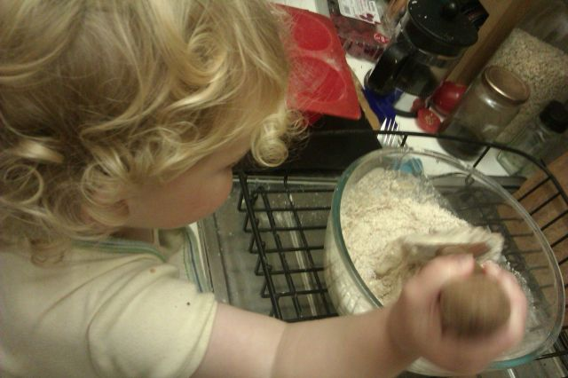 """Small child stirs a bowl of muffin mixture"""