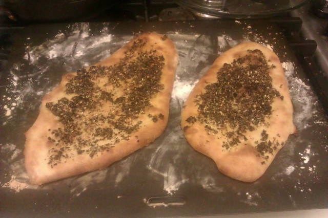 """2 pieces of flatbread with a green herb mix on top"""